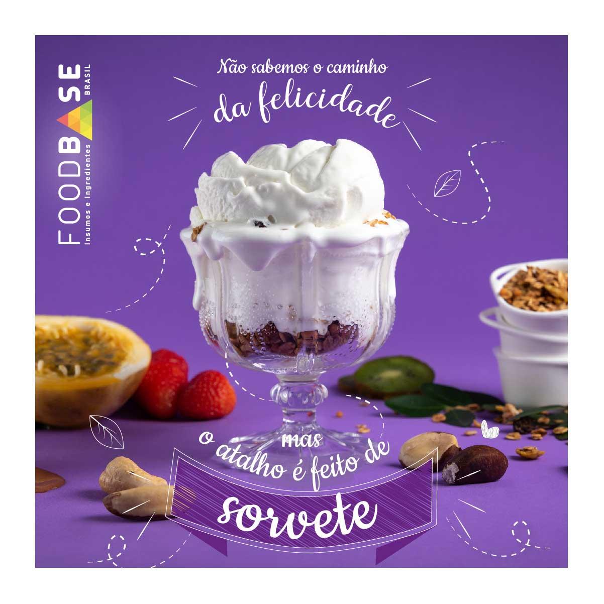 Sorvete de Iorgute italino na taça, feito com os produtos Foodbase. Compõe a cena, fundo lilás, frutas e granola e ainda a frase: &quote;Não sabemos o caminho da felicidade mas no atalho tem sorvete.&quote;